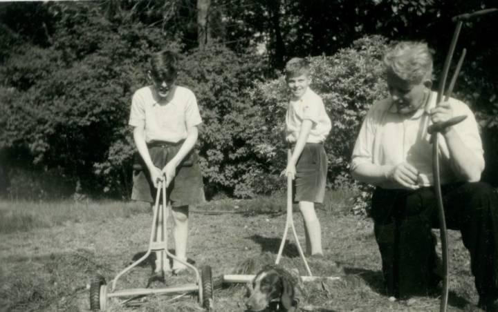 Jan (l) en Bert (r) assisteren vader bij het maaien van het gazon.